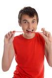 Muchacho sonriente que come el caramelo Imagenes de archivo