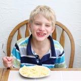 Muchacho sonriente que come las pastas Fotos de archivo libres de regalías