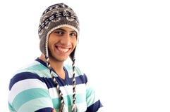 Muchacho sonriente que cubre su cabeza con el casquillo de lana Fotografía de archivo
