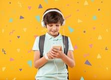 Muchacho sonriente que escucha la música y la mirada de la pantalla de su dispositivo Fotografía de archivo libre de regalías