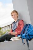 Muchacho sonriente que estudia sentarse en la pared de la escuela Imagen de archivo