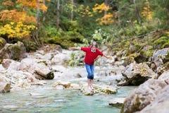 Muchacho sonriente que intenta cruzar el río salvaje de la montaña Fotografía de archivo libre de regalías
