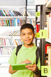 Muchacho sonriente que juega con la tableta en biblioteca Imágenes de archivo libres de regalías