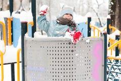 Muchacho sonriente que juega con nieve Imágenes de archivo libres de regalías