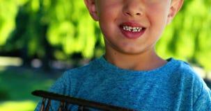Muchacho sonriente que juega con un avión del juguete en parque metrajes