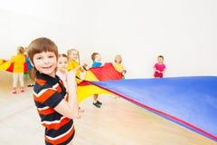 Muchacho sonriente que juega el paracaídas con los amigos en gimnasio Fotos de archivo