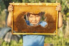 Muchacho sonriente que lleva a cabo el marco del panal Foto de archivo libre de regalías