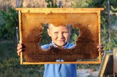 Muchacho sonriente que lleva a cabo el marco del panal Imágenes de archivo libres de regalías