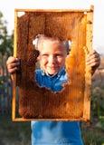 Muchacho sonriente que lleva a cabo el marco del panal Fotos de archivo