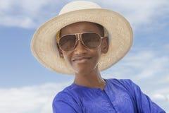 Muchacho sonriente que lleva un sombrero de paja del navegante y un par de gafas de sol Fotos de archivo libres de regalías