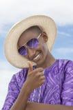 Muchacho sonriente que lleva un sombrero de paja del navegante y un par de gafas de sol Foto de archivo
