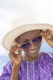 Muchacho sonriente que lleva un sombrero de paja del navegante y un par de gafas de sol Foto de archivo libre de regalías