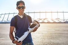 Muchacho sonriente que mantiene el gyroscooter al aire libre Imágenes de archivo libres de regalías