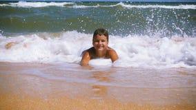Muchacho sonriente que miente en la playa en la resaca almacen de metraje de vídeo