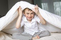 Muchacho sonriente que oculta en cama debajo de una manta o de una sobrecama blanca Fotografía de archivo libre de regalías