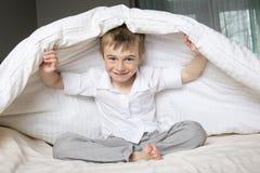 Muchacho sonriente que oculta en cama debajo de una manta o de una sobrecama blanca Fotografía de archivo