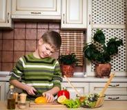 Muchacho sonriente que prepara una ensalada en la cocina. fotos de archivo libres de regalías