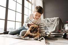 Muchacho sonriente que rasguña la cabeza de su animal doméstico Fotos de archivo libres de regalías