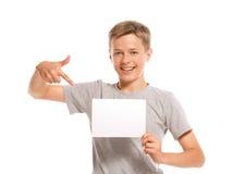 Muchacho sonriente que señala en el papel en blanco blanco Foto de archivo