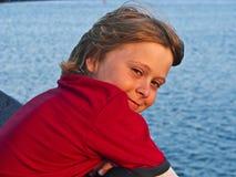 Muchacho sonriente que se coloca en un embarcadero Fotos de archivo
