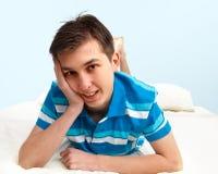 Muchacho sonriente que se reclina sobre cama Fotografía de archivo libre de regalías