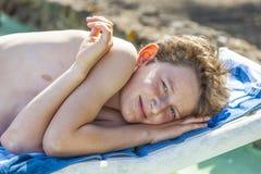 Muchacho sonriente que se relaja en un sunlounger Fotografía de archivo