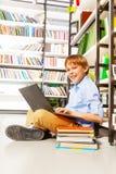 Muchacho sonriente que se sienta con el ordenador portátil en el piso Imagen de archivo libre de regalías
