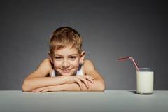 Muchacho sonriente que se sienta con el vidrio de leche Fotos de archivo libres de regalías
