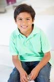 Muchacho sonriente que se sienta en el sofá foto de archivo libre de regalías
