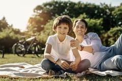 Muchacho sonriente que se sienta en la hierba con su papá Fotografía de archivo libre de regalías