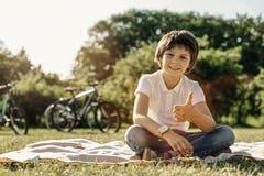 Muchacho sonriente que se sienta en la hierba y que muestra el pulgar para arriba Imagen de archivo