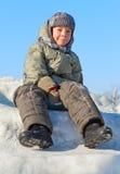 Muchacho sonriente que se sienta en la nieve Foto de archivo