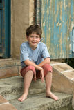 Muchacho sonriente que se sienta en pasos de progresión Foto de archivo