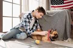 Muchacho sonriente que se sienta en semi la posición con su animal doméstico Foto de archivo libre de regalías