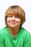 Muchacho sonriente que se sienta en un sofá Fotos de archivo