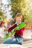 Muchacho sonriente que se sostiene con el monopatín verde de los brazos Imágenes de archivo libres de regalías