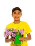 Muchacho sonriente que sostiene el cubo con los tulipanes rosados Foto de archivo libre de regalías