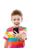 Muchacho sonriente que sostiene el teléfono móvil o smartphone que toma a uno mismo Foto de archivo