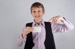 Muchacho sonriente que sostiene la tarjeta de banco blanca y que muestra en ella por el finger Fotografía de archivo libre de regalías