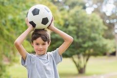 Muchacho sonriente que sostiene un balón de fútbol en el parque Imagenes de archivo