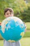 Muchacho sonriente que sostiene un globo de la tierra en el parque Fotos de archivo libres de regalías