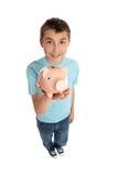 Muchacho sonriente que sostiene un rectángulo de dinero rosado del cerdo Fotos de archivo libres de regalías