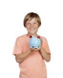 Muchacho sonriente que sostiene una hucha azul Imágenes de archivo libres de regalías