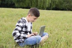 Muchacho sonriente que usa el ordenador portátil moderno Fotografía de archivo libre de regalías