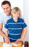 Muchacho sonriente y su padre que preparan el desayuno Imagen de archivo libre de regalías