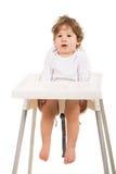 Muchacho sorprendente que se coloca derecho en silla Imagen de archivo