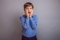 Muchacho sorprendido del adolescente en fondo gris Fotos de archivo libres de regalías