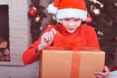 Muchacho sorprendido del niño que sostiene el regalo de la Navidad en sitio Fotografía de archivo libre de regalías