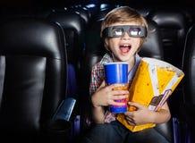 Muchacho sorprendido que mira la película 3D en teatro Fotografía de archivo
