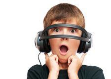 Muchacho sorprendido que mira a través de los auriculares Imagenes de archivo